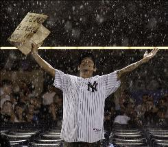 A Yankees fan stands in a downpour during a rain delay in the fifth inning. The game between New York and Kansas City was delayed for 1 hour, 25 minutes by a nasty thunderstorm.