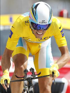 Spain's Alberto Contador, wearing the overall leader's yellow jersey, strains as he crosses the finish line during the 19th stage, an individual time trial over 32.3 miles from Bordeaux to Pauillac, France.