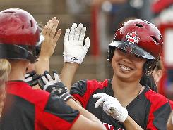 Canada's Jennifer Yee celebrates with her team after scoring a run in the second inning of their game against the U.S. at the World Cup of Softball in Oklahoma City on Sunday. Canada defeated the U.S. 5-2.