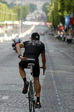 "Lance Armstrong, wearing his black jersey with ""28"" on the back, parades for the last time on Champs-Elysees Avenue at the end of the last stage of the 2010 Tour de France. Radioshack riders had to remove their Livestrong tee-shirts to put on official ones for not the team to be disqualified from the race."