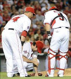 Angels starter Dan Haren, center, is checked on by Mike Napoli, left and Jeff Mathis after being hit by a line drive off the bat of Kevin Youkilis during the fifth inning.