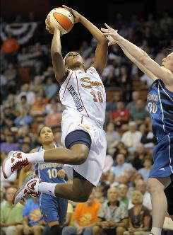 Connecticut Sun's Asjha Jones drives to the hoop while guarded by Washington Mystics' Katie Smith during the first half of their game in Uncasville, Conn., on Tuesday.