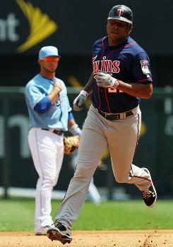 Delmon Young rounds the bases after hitting a three-run home run in the first inning to give the Twins an early lead against the Royals.