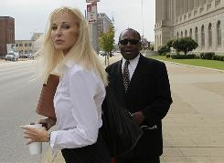 Karen Sypher stands with Rev. William Franklin outside the federal courthouse after listening to a day of testimony in her extortion trial in Louisville, on Wednesday.