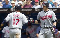 Indians' Shin-Soo Choo, left, is congratulated by teammate Chris Gimenez after being walked in with the bases loaded by Blue Jays pitcher Brett Cecil during the fourth inning.