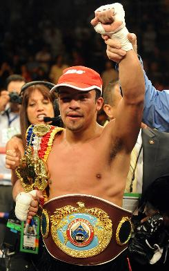 Juan Manuel Marquez celebrates after defeating Juan Diaz to keep his WBA and WBO lightweight championship belts.