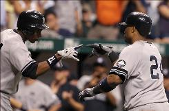 Curtis Granderson, left, congratulates Robinson Cano after Cano hit a tie-breaking solo home run in the top of the ninth inning.