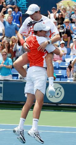 Mike Bryan jumps into the arms of brother Bob Bryan after the duo collected their record- breaking 62nd ATP Tour doubles title on Sunday against Eric Butorac and Jean-Julien Rojer at the Farmers Classic in Los Angeles.