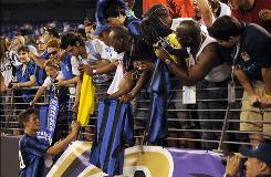 Inter Milan's Cristian Chivi autographs fans' items after his team's victory over Manchester City in Baltimore on Saturday.