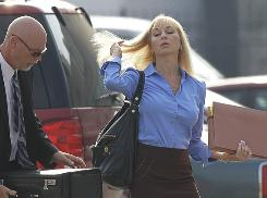 "Karen Sypher arrives at the federal courthouse in Louisville with her attorney, James Earhart, on July 27. Sypher's trial, now in its second week, continued on Monday with a witness testifying that Sypher told him after she was indicted that she had done something ""stupid."""