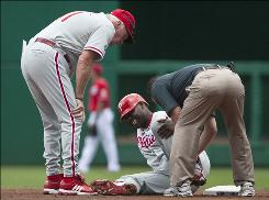 Phillies manager Charlie Manuel looks over injured first baseman Ryan Howard during Sunday's game with the Nationals. Howard was placed on the disabled list Tuesday with a sprained left ankle.