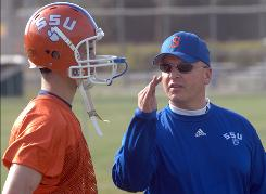 "Former Savannah State coach Robby Wells, who resigned in January, is suing the school for racial discrimination. Junior quarterback A.J. Defilippis, left, says, ""We were left in the dark on so many things. ... I'm still not sure what happened, but I want to stay."""
