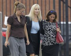 Karen Sypher, center, leaves the federal courthouse in Louisville with two unidentified women after a jury found her guilty of extorting Louisville basketball coach Rick Pitino.
