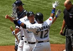 Edwin Encarnacion congratulates Blue Jays catcher J.P. Arencibia after his second-inning homer against Tampa Bay.