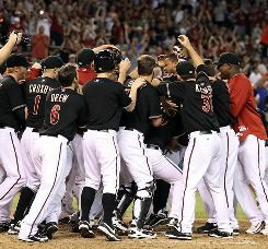 The Diamondbacks mob Chris Young after the outfielder's walk-off home run in the bottom of the ninth.