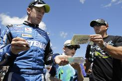 Carl Edwards signs autographs for fans after winning the pole at Watkins Glen International.