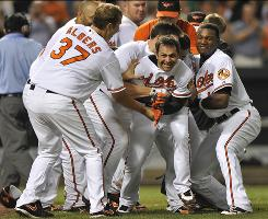 The Orioles mob teammate Brian Roberts, center, after Roberts hit a game-winning solo home run against the White Sox in the 10th inning.