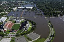 In Ames, Squaw Creek crest has caused flooding at Jack Trice Stadium, left, and Hilton Coliseum, top. The Ames emergency operations center is open and city officials are closing streets due to high water.