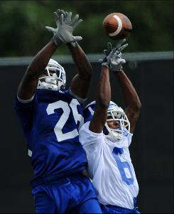 Defensive back Jamal Ransby, left, battles Darren McCray for the ball during Georgia State University's first football practice to prep its inaugural season.