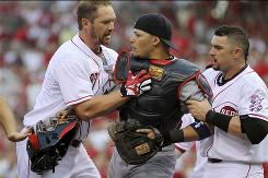 The Reds' Scott Rolen, left, and Jonny Gomes, right, pull Cardinals catcher Yadier Molina away from batter Brandon Phillips during an altercation in the first inning.