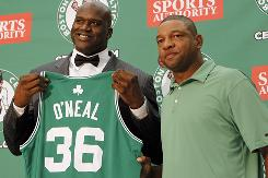 New Celtic Shaquille O'Neal shows off his new jersey with Boston head coach Doc Rivers by his side.