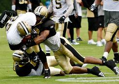 Saints safety Usama Young, right, hits running back Reggie Bush during a workout early in camp.