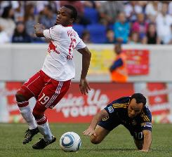 The Red Bulls' Dane Richards, left, plays the ball as the Galaxy's Landon Donovan falls to the ground during their MLS game in Harrison, N.J. Los Angeles beat New York 1-0, making an Edson Buddle goal from the 10th minute stand up.