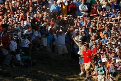 "Dustin Johnson watches his second shot on the 18th hole, surrounded by a crowd, during the final round of the 92nd PGA Championship. Johnson was penalized for grounding his club in a bunker. ""It never once crossed my mind that I was in a sand trap,"" Johnson said."