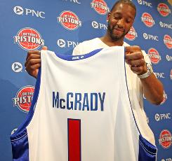 Newly signed free agent Tracy McGrady checks out his new Pistons jersey during a news conference at the team's practice facility.
