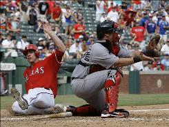 The Rangers' Taylor Teagarden slides into home, beating the throw to Red Sox catcher Jarrod Saltalamacchia during the eighth inning.