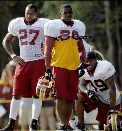 Washington Redskins running backs Larry Johnson, left, Clinton Portis, center, and Willie Parker look on during the team's training camp at Redskins Park in Ashburn, Va., Aug. 10.