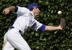 Chicago Cubs right fielder Xavier Nady misses a fly ball in Wrigley Field during a game this month with Cincinnati. Some players theorize that certain aspects of the ballpark and the Cubs' schedule make it more difficult for them to win at home.