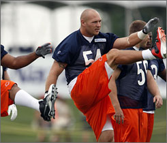 Brian Urlacher, out for 15 games last season, is back on a Bears defense that has also added pass rusher Julius Peppers.