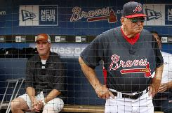 After having season ending surgery, Braves' Chipper Jones, left, sits in the dugout as manager Bobby Cox watches over batting practice.