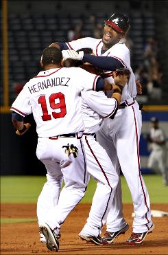 Braves outfielder Jason Heyward, right, celebrates with teammates Melky Cabrera, center, and Diory Hernandez after driving in the game-winning run in the ninth inning against the Nationals.