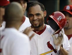 The Cardinals' Pedro Feliz is congratulated by teammates in the dugout after scoring on a double by Brendan Ryan during the fifth inning. Feliz went 2-for-4 and drove in two runs.