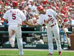 Cardinals third baseman Pedro Feliz (77) greets teammate Albert Pujols on his way back to the dugout after he scored on a sacrifice fly in the third inning.