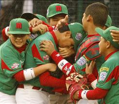 Nuevo Laredo, Mexico pitcher Eduardo Mata, center, is swarmed by teammates after leading his team to a 4-2 win over Manati, Puerto Rico.