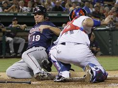 Rangers catcher Bengie Molina tags out the Twins' Danny Valencia during the seventh inning. The Rangers edged the Twins 4-3.