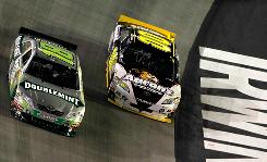 David Reutimann (00) works to the inside of Kyle Busch during their late-race contest for the lead at Bristol Motor Speedway.