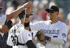 Carlos Gonzalez, right, celebrating with teammates after the Rockies rallied from nine runs down to shock the Braves with a 12-10 win, hit a two-run, game-tying single in the eighth inning.