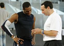 "Team USA head coach Mike Krzyzewski, right, talks things over with guard Rajon Rondo in between practice drills last week in Madrid. ""Rajon came to us and said he ... had some family matters to attend to,"" USA Basketball Chairman Jerry Colangelo said about the guard's decision to withdraw."