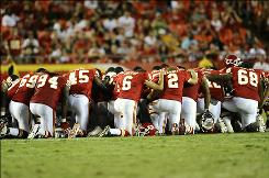 Kansas City Chiefs players gather on the field to pray for Cameron Sheffield, who was carted off the field during a preseason game against the Philadelphia Eagles.