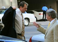 Roger Clemens puts on his coat as he arrives at the U.S. District Court in Washington, DC. Attorney Rusty Hardin is with the former pitcher.