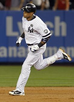 Yankees' Robinson Cano rounds the bases after his solo home run in the third inning against the Athletics.