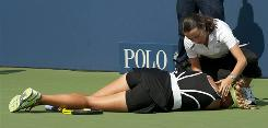A trainer rushes to assist Victoria Azarenka of Belarus, who collapsed to the court during her match against Gisela Dulko of Argentina on Wednesday at the U.S. Open.