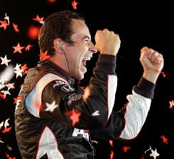 Helio Castroneves celebrates in victory lane after winning the IndyCar Series Kentucky Indy 300, his first victory since April.