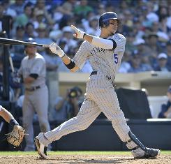 Carlos Gonzalez follows through on a two-run double in the eighth inning against the Padres. Gonzalez extended his hitting streak to 12 games, and the Rockies beat the Padres for the 10th time in 14 games this season.