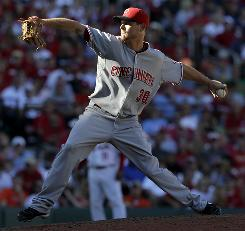 Reds pitcher Travis Wood threw seven solid innings and hit his first career home run to help Cincinnati extend its lead over St. Louis in the NL Central.