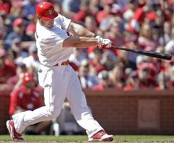Cardinals outfielder Matt Holliday connects for a three-run home run in the sixth inning against the Reds.